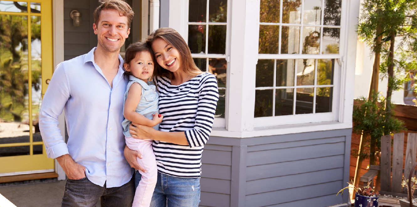A couple with their young daughter are standing outside of their newly purchased home and smiling at the camera.